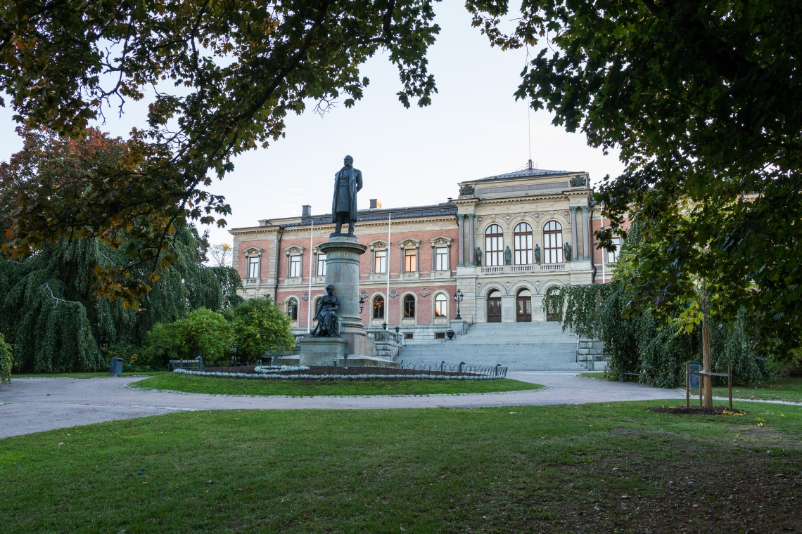 University Main Building in Uppsala with trees and a statue in th foreground.